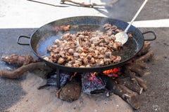 Piernas de pollo frito Preparación de la paella del pollo el plato español nacional de la paella en una sartén grande se cocina e Imagen de archivo libre de regalías