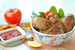 Piernas de pollo frito y alas apetitosas en placa cerca de la salsa de tomate, especias Imagen de archivo libre de regalías