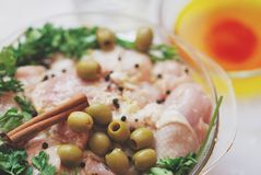 Piernas de pollo, perejil, canela y especias crudos en el plato de cristal en la tabla blanca, cierre para arriba Fotos de archivo
