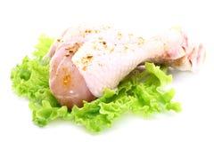 Piernas de pollo sin procesar con la ensalada verde Foto de archivo