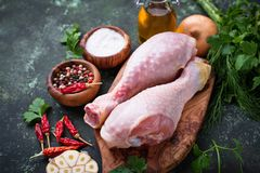 Piernas de pollo sin procesar con las especias y el ajo Imagen de archivo libre de regalías