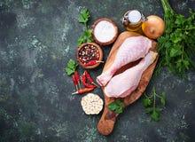 Piernas de pollo sin procesar con las especias y el ajo Imagenes de archivo