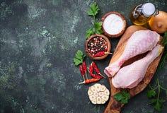 Piernas de pollo sin procesar con las especias y el ajo Foto de archivo