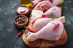 Piernas de pollo sin procesar con las especias y el ajo Foto de archivo libre de regalías