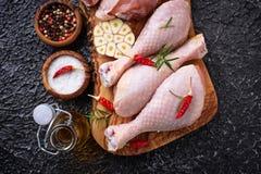 Piernas de pollo sin procesar con las especias y el ajo Fotos de archivo
