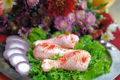 Piernas de pollo sin procesar dispuestas con la ensalada fresca Fotografía de archivo