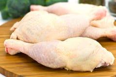 Piernas de pollo sin procesar en la tarjeta de madera Imagenes de archivo
