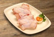 Piernas de pollo sin procesar frescas en tarjeta de madera Imagen de archivo libre de regalías