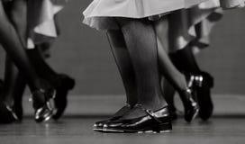 Piernas de un bailarín de golpecito en zapatos negros clásicos Imagen de archivo libre de regalías