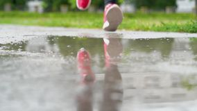 Piernas de un corredor en zapatillas de deporte Aire libre que activa de la mujer de los deportes, caminando en charco fangoso So almacen de metraje de vídeo