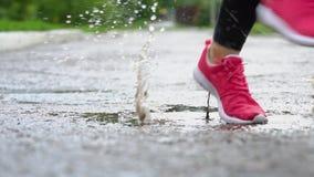 Piernas de un corredor en zapatillas de deporte Aire libre que activa de la mujer de los deportes, caminando en charco fangoso So almacen de video