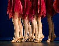 Piernas de un grupo de bailarinas en faldas rojas Imagenes de archivo