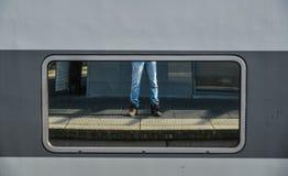 Piernas de un hombre en mezclilla y zapatillas de deporte fotos de archivo