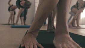 Piernas de un hombre que hace asana de la yoga Trikonasana