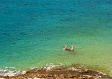 Piernas de un hombre que salta en el mar foto de archivo