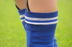 Piernas de un muchacho del fútbol Foto de archivo