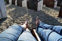 Piernas de un par en los vaqueros que se sientan descalzo en una silla de playa imágenes de archivo libres de regalías