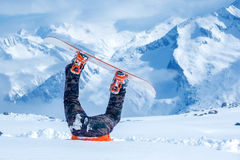 Piernas de un snowboarder pegado en nieve imagen de archivo