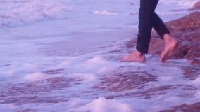 Piernas de una chica joven que camina en la piedra de tierra, playa, ondas con espuma en la salida del sol almacen de metraje de vídeo