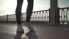 Piernas de una muchacha en zapatillas de deporte de los deportes en el puente metrajes