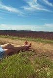 Piernas de una mujer caucásica joven cerca de un camino de tierra Fotografía de archivo libre de regalías