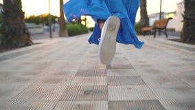 Piernas de una mujer en un vestido azul hermoso que corre a lo largo de la avenida de la palma El sombrero baja a la tierra metrajes