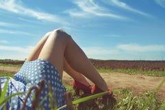 Piernas de una mujer joven cerca de un camino de tierra Foto de archivo libre de regalías