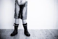 Piernas del adolescente con los pantalones y las botas mojados Imagen de archivo