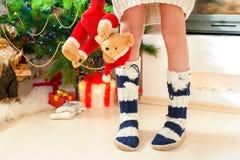 Piernas del adolescente en calcetines de lana calientes acogedores con los pompones Fotos de archivo