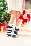 Piernas del adolescente en calcetines de lana calientes acogedores con los pompones Fotos de archivo libres de regalías