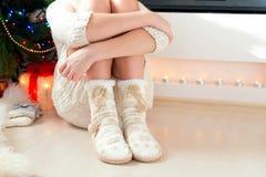 Piernas del adolescente en calcetines de lana calientes acogedores con los pompones Foto de archivo