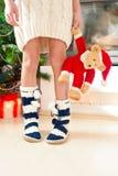 Piernas del adolescente en calcetines de lana calientes acogedores con los pompones Imagen de archivo libre de regalías