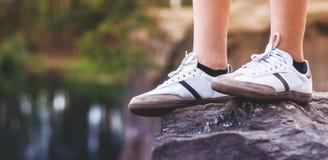Piernas del adolescente en las zapatillas de deporte blancas en una roca Foto de archivo