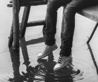 Piernas del adolescente que se sientan en el muelle de madera Fotografía de archivo