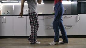 Piernas del baile feliz de los pares en cocina almacen de metraje de vídeo