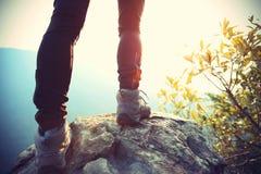Piernas del caminante de la mujer joven en pico de montaña de la salida del sol Fotografía de archivo