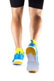 Piernas del corredor en zapatillas de deporte en un fondo blanco imágenes de archivo libres de regalías