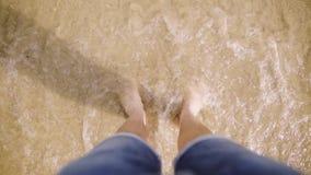 Piernas del hombre caucásico bronceado en la playa arenosa en la playa, arriba encima de la visión Vaqueros que llevan del hombre almacen de metraje de vídeo