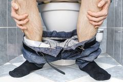 Piernas del hombre con la diarrea que se está sentando en retrete imágenes de archivo libres de regalías