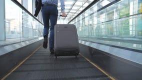 Piernas del hombre de negocios acertado que corren en el pasillo del terminal y que tiran de la maleta en las ruedas La cámara si almacen de metraje de vídeo