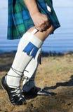 Piernas del hombre en falda escocesa Foto de archivo libre de regalías