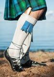 Piernas del hombre en falda escocesa escocesa Imagenes de archivo