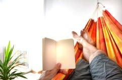 Piernas del hombre que se acuestan en la hamaca interior que sostiene el libro de aviso vacío en su mano Foto de archivo libre de regalías