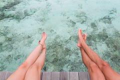 Piernas del hombre y de la mujer asentadas en un embarcadero sobre el agua azul clara imágenes de archivo libres de regalías