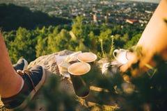 Piernas del hombre y de la mujer en el top de la colina con dos tazas y chocolates Imagen de archivo libre de regalías