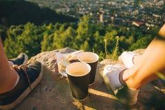 Piernas del hombre y de la mujer en el top de la colina con dos tazas y chocolates Fotos de archivo libres de regalías