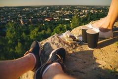Piernas del hombre y de la mujer en el top de la colina con dos tazas y chocolates Fotografía de archivo