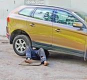 Piernas del mecánico que repara el coche Foto de archivo libre de regalías