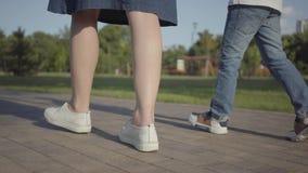 Piernas del primer de los niños de los hermanos que caminan llevando a cabo las manos en el parque del verano Ocio al aire libre  almacen de video