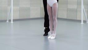 Piernas del primer de pequeñas bailarinas en los zapatos blancos que equilibran con el profesor que ayuda en estudio del ballet metrajes